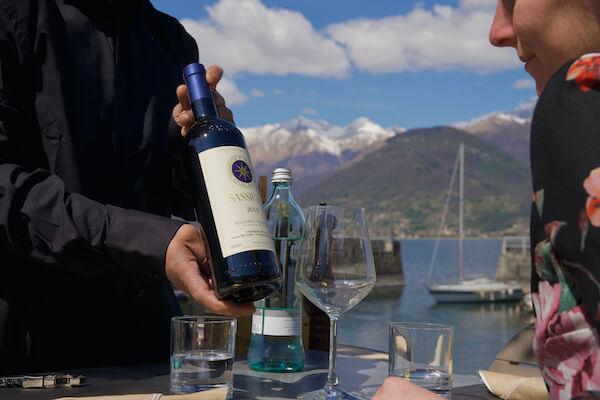Cameriere che serve un vino della Valtellina al ristorante sul Lago di Como